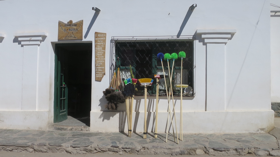 Brooms and feather dusters for sale outside a hardware store in Cachi.