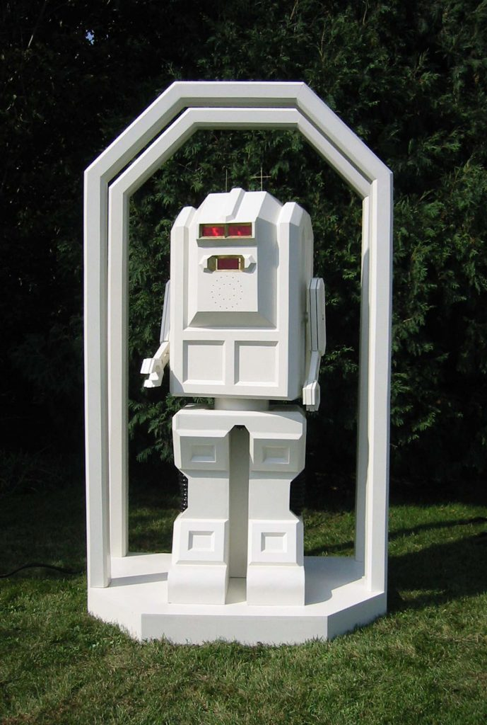 Stone built the Nuptron 4000 to officiate his own wedding ceremony in 2004. The Nuptron speaks, moves arms, and pivots at waist; his eyes flash when speaking, and his mouth is an LCD screen with a single white line that modulates according to sound emitted.