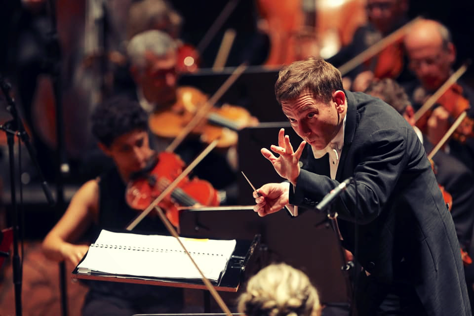 Daniel Smith conducting the orchestra.