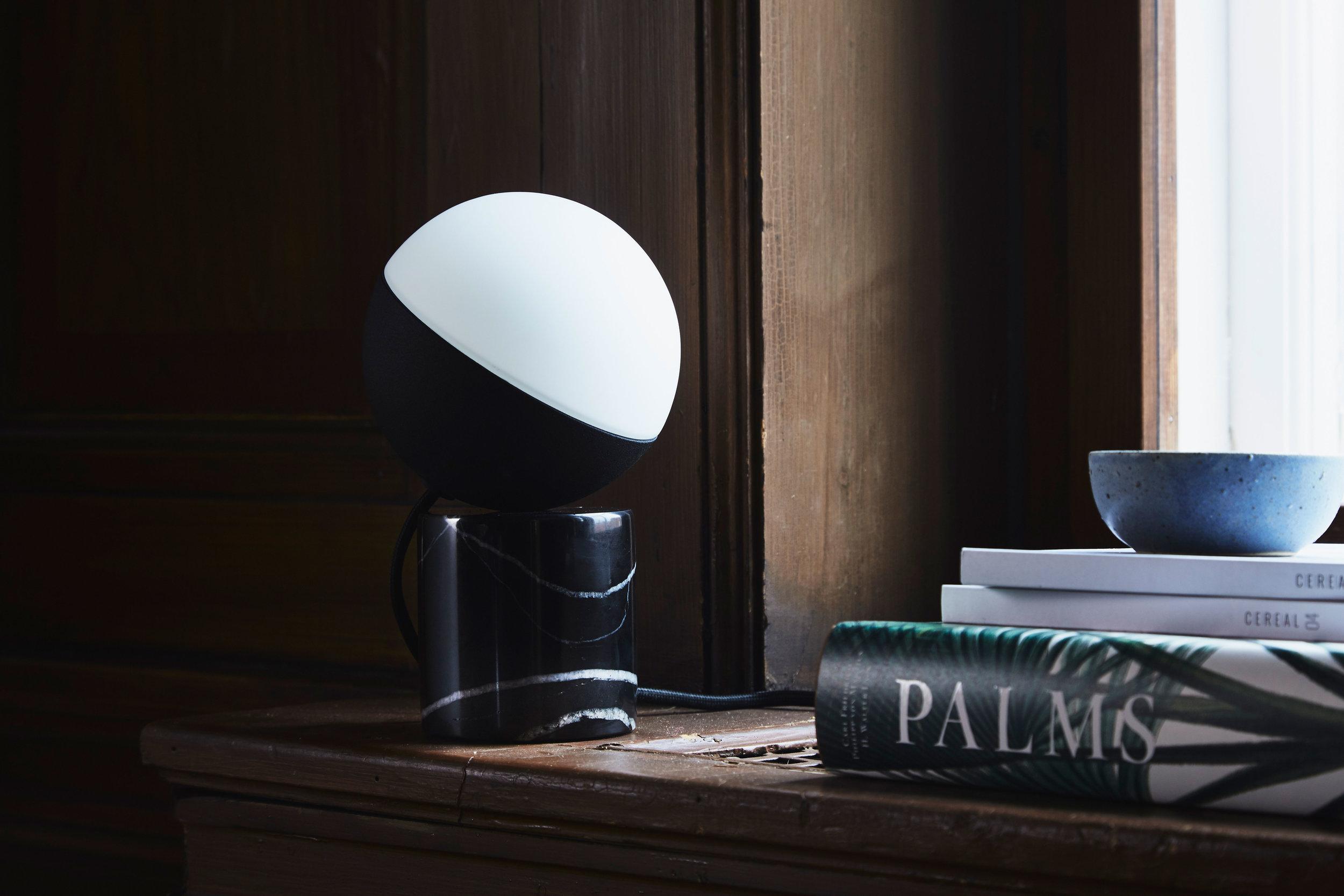 Table lamp with black fabric cord. Dimensions: H20 cm Variants: Black Marble | Concrete  Designer: Frandsen Design Studio    MORE