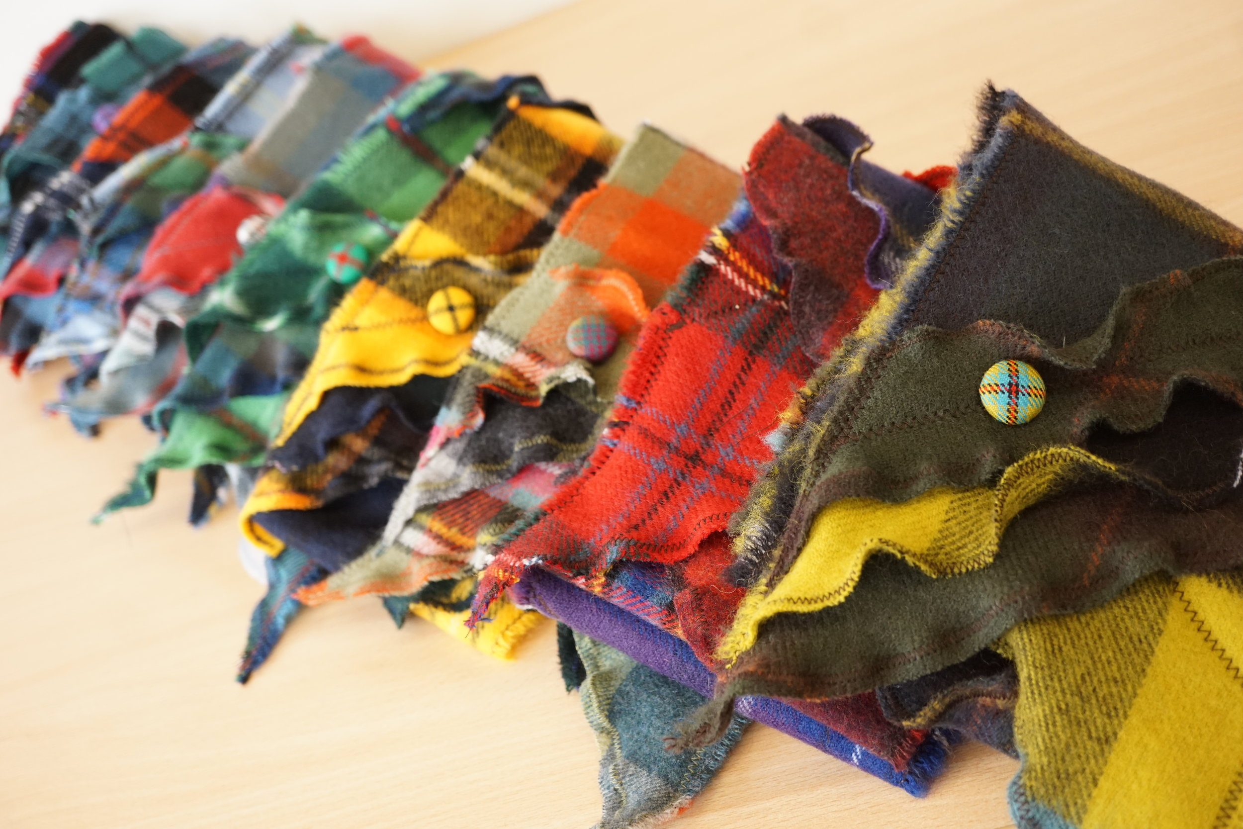 Brislin Scarves - The Brislin Scarf are made from the softest wool fabrics and are made with little panels with crinkles and are finished off with some hand-covered buttons. Lots of colour and texture to keep you cosy.
