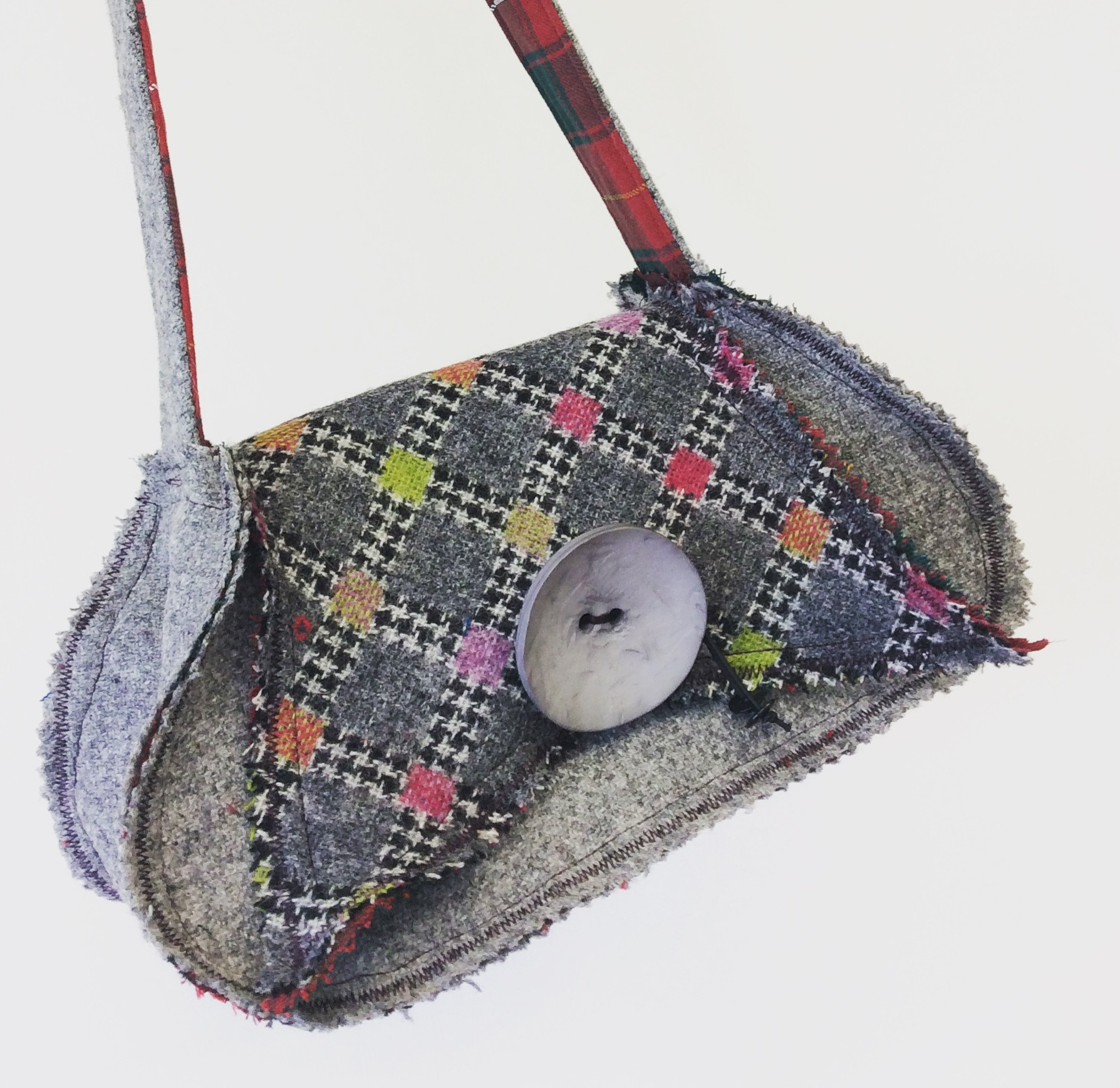 Wee Tatterwallop - The wee Tatterwallop meaning small ragged garment are small shoulder bags with most of their seams on the outside giving them a distinctive casual look. They are fully lined with two internal pockets. One with a hand-covered button closure and they are finished off with large over-sized button and strong elastic closure.