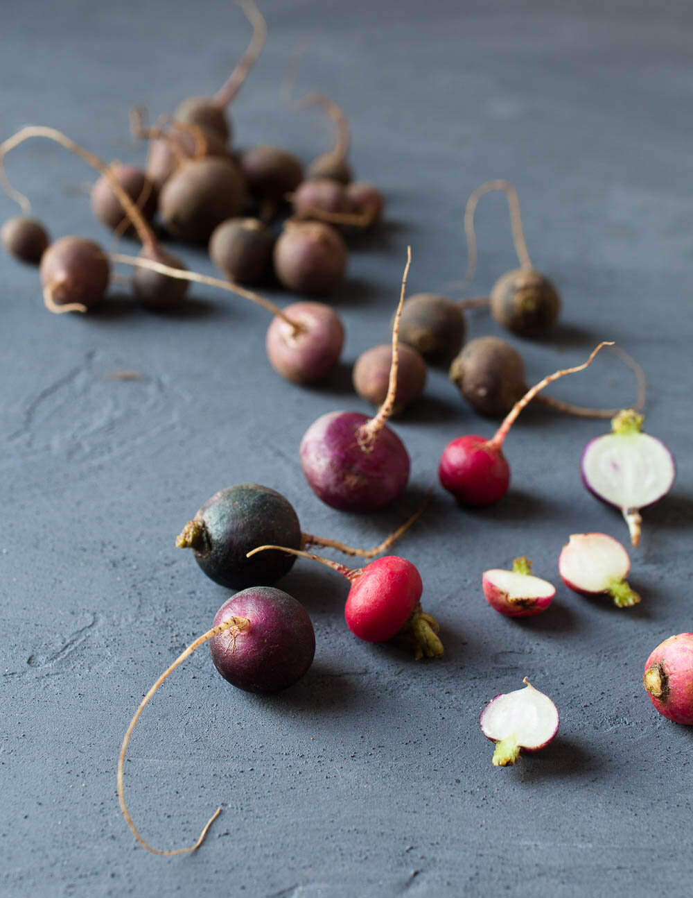 photograph of purple and red radishes from muddy to clean on textured background