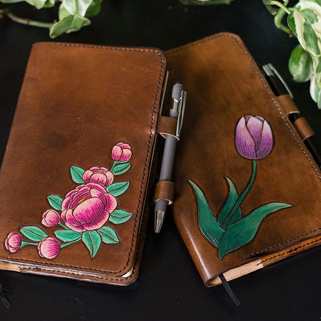 Hand tooled and painted leather journals! Coming in July. 💜💚💖 #handmade #leathercraft #tooledleather #buffalolucy #flowerpower #supportqueerartists #pdxmakers #handmadelife #picoftheday #beauty #tattoostyle #natureinsipred #love