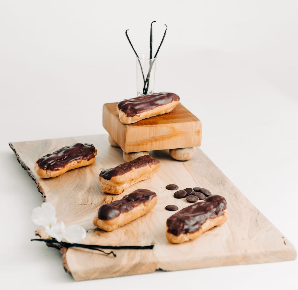 Eclairs - Light pate-a-choux filled with vanilla pastry cream and glazed with chocolate ganache. Our namesake pastry!