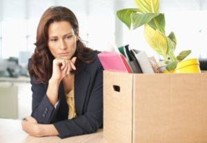 Contemplative businesswoman with office supply in cardboard box
