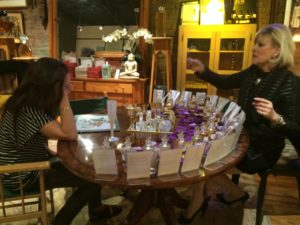 Sue Phillips, founder and CEO of Scenterprises, assists actress Katie Holmes creating a fragrance at Scentorium.