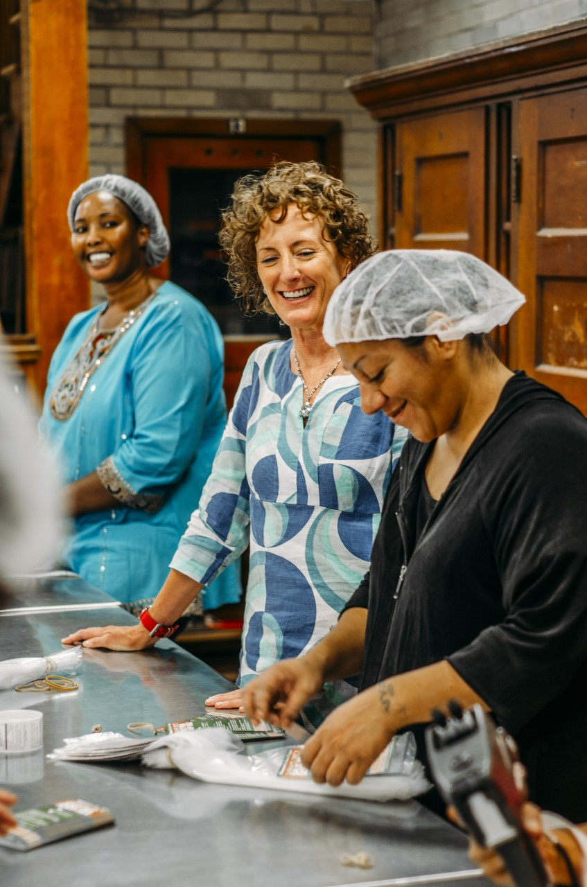 Tamra Ryan (center), CEO of Women's Bean Project with workers Abok (left) and Emilia (right.)