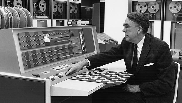 "Arthur Samuels, who coined the phrase ""machine learning,"" works with an early IBM machine and a checkerboard."