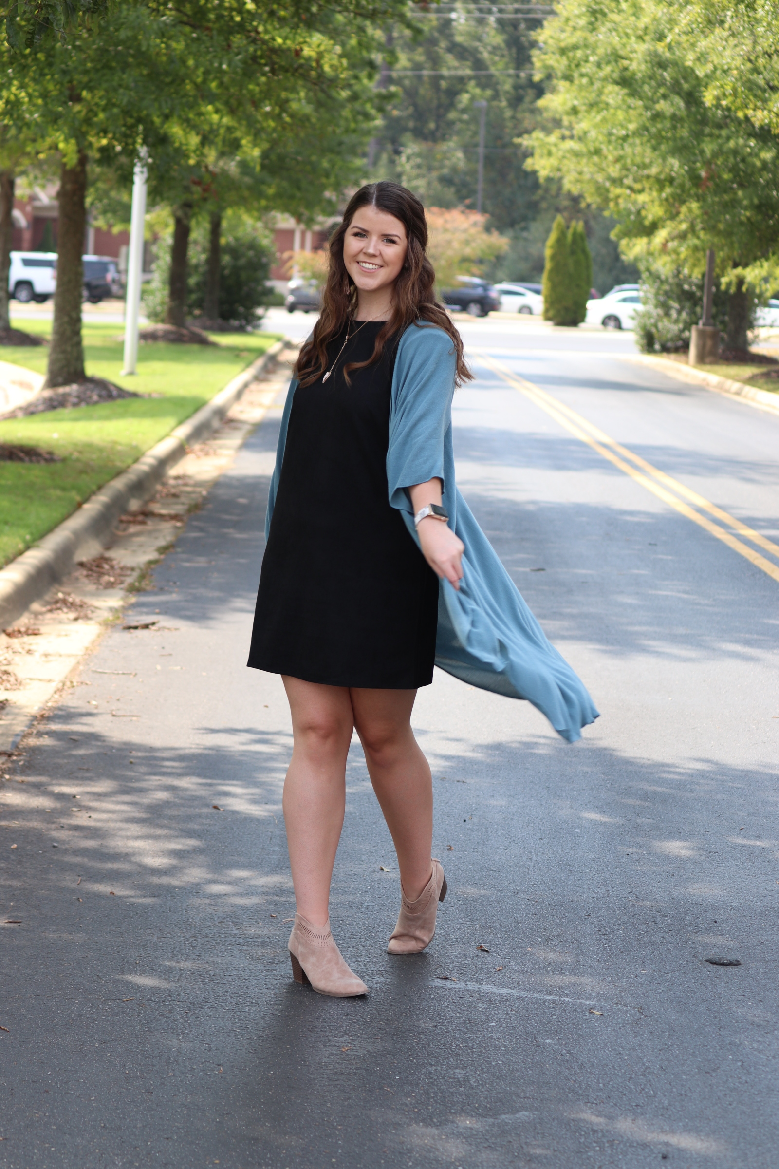 This weather has twirling with excitement! Kailey's look is a little dressier and perfect for work, church, fall weddings or showers. This black dress is a thicker material and we love the blue kimono paired with it!  Find this look in store, or call to order.