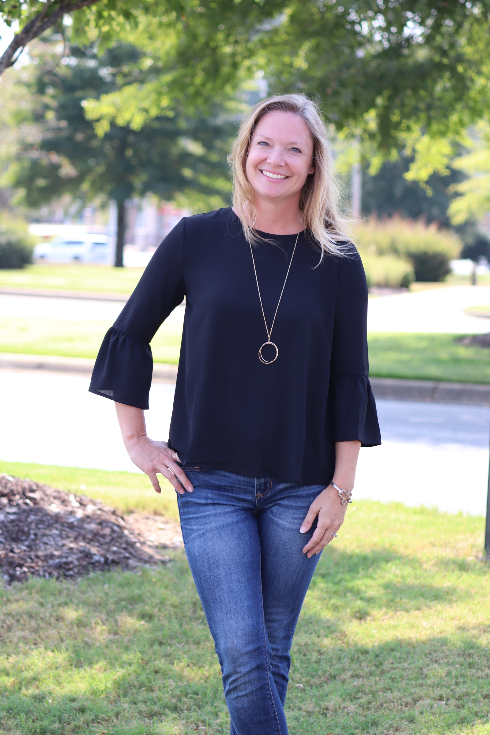 Kristin has on our classic black bell sleeve top. We also have this available in crimson and both colors are perfect for gameday or holiday festivities! We love how she paired it with a long ABLE necklace. They make great gifts too!