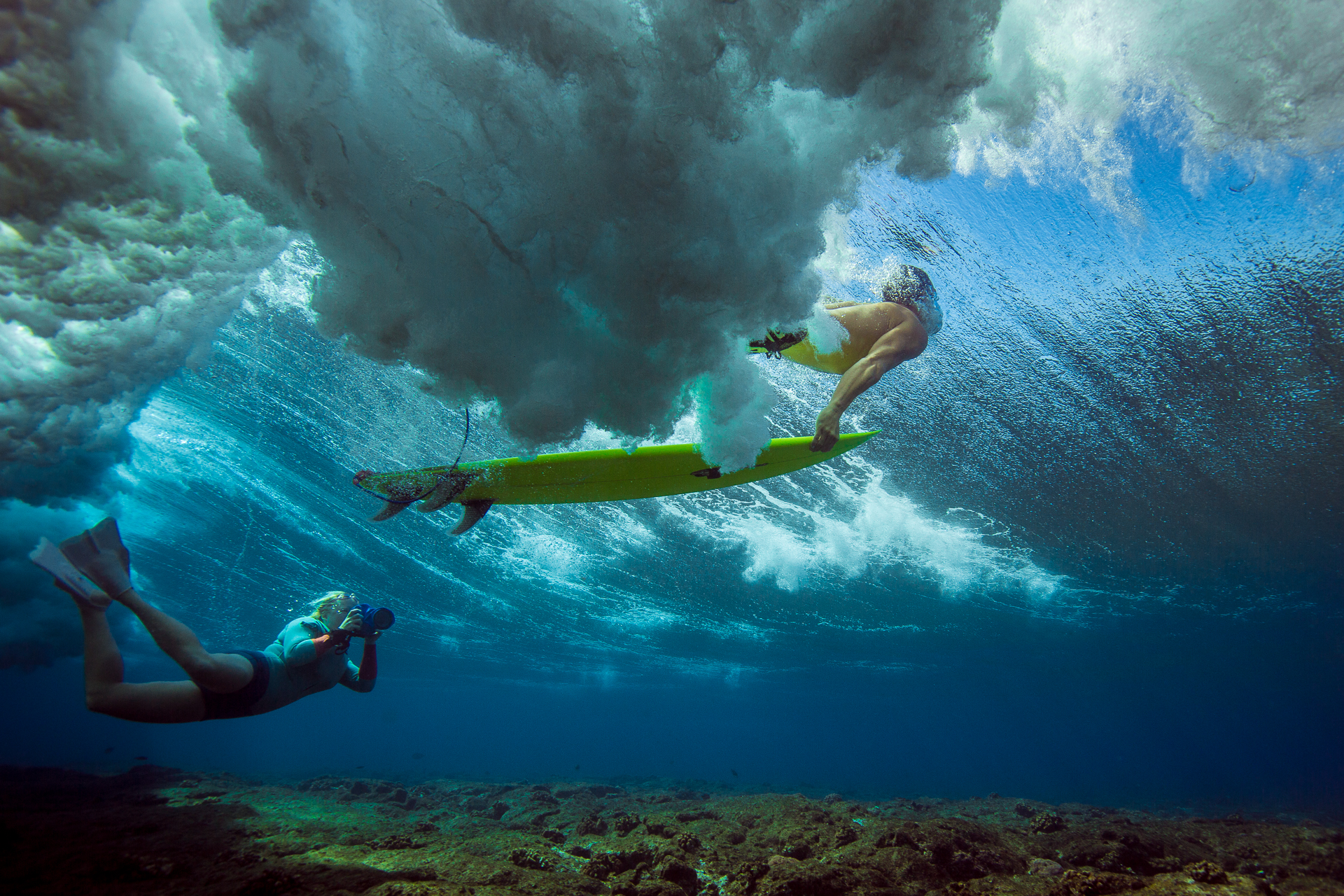 Sarah Lee photographing a surfer duck diving underwater with the original blue Outex cover. (Photo: Mark Tipple)