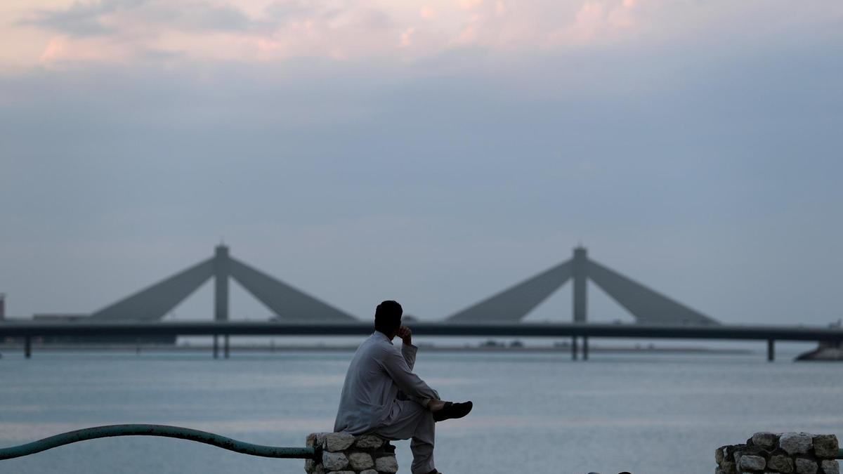 FILE-PHOTO-Man-sits-and-looks-towards-the-Sheikh-Isa-Causeway-in-Manama.jpg