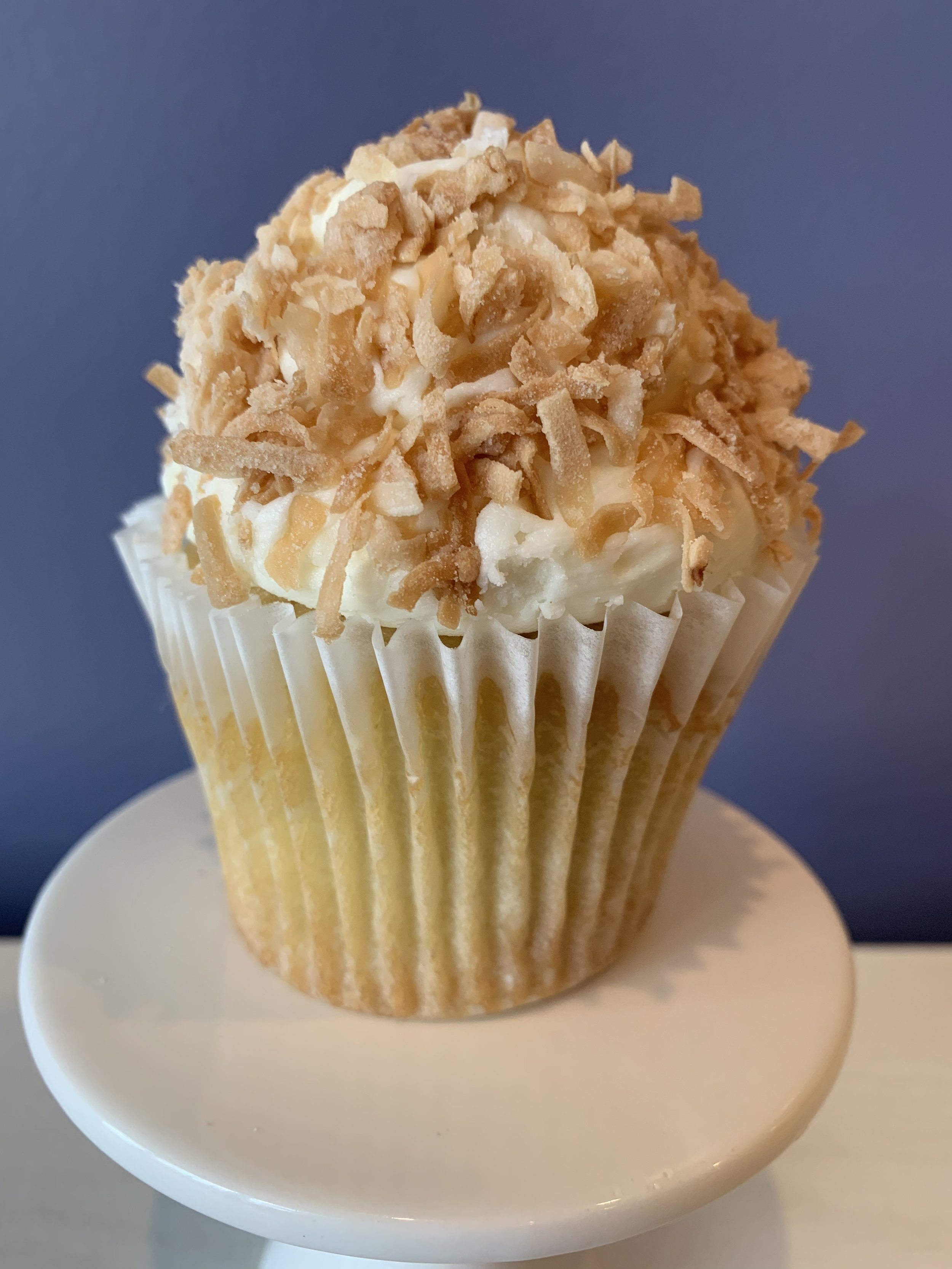 Coconut Cream Pie - Coconut cake filled with vanilla pastry cream topped with coconut buttercream and rolled in toasted coconut.