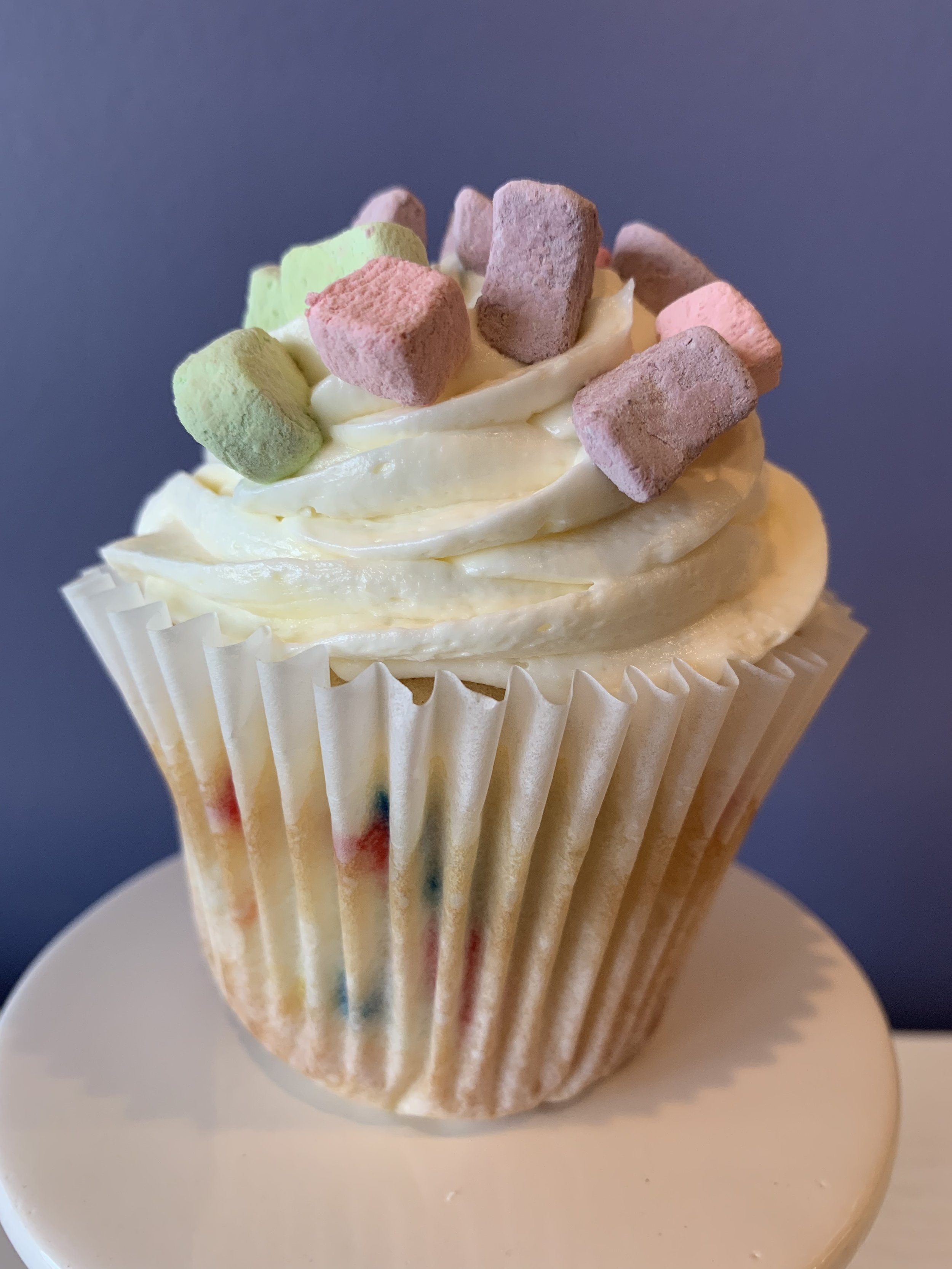 Lucky Charms - White cake with rainbow sprinkles in the batter topped with marshmallow buttercream and lucky charm marshmallows.Vegan and Gluten Free available