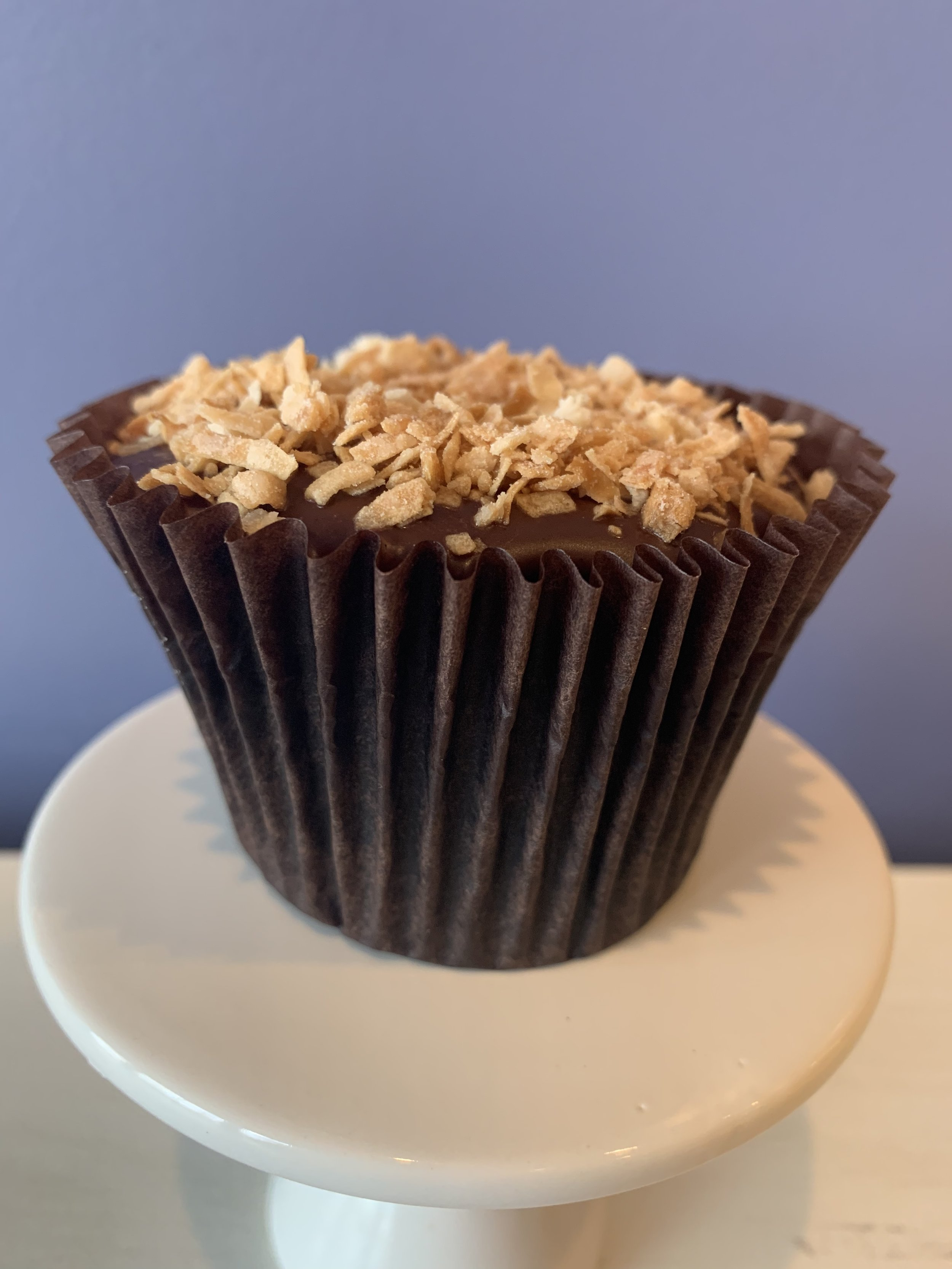 Mallow Cup - Double chocolate cake filled with marshmallow buttercream topped with chocolate glaze and toasted coconut.