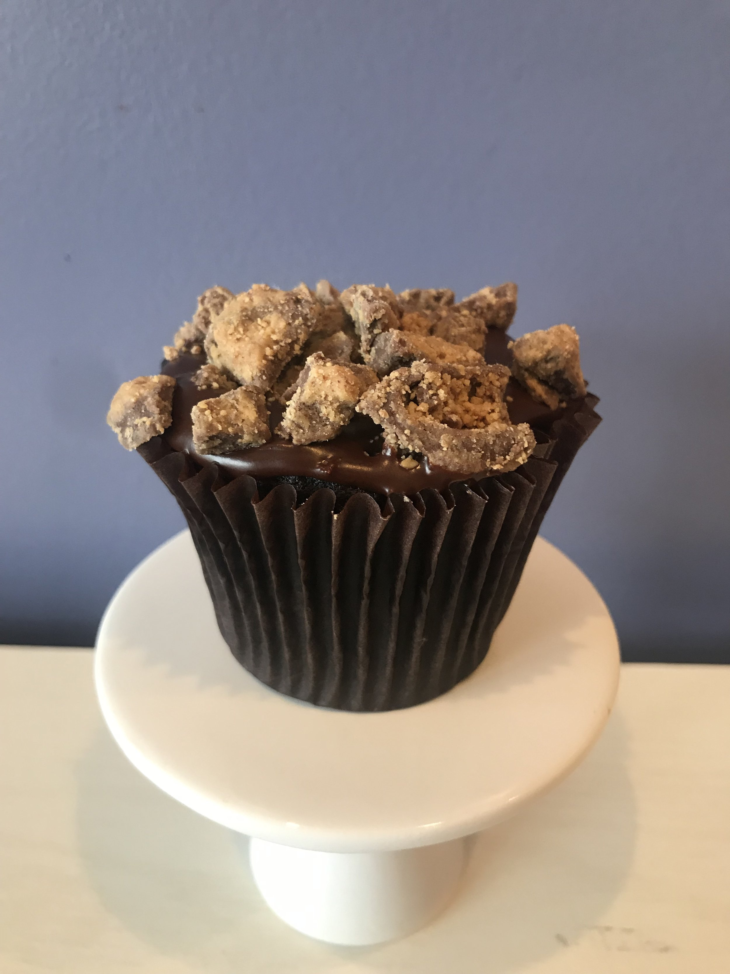 Peanut Butter Cup Craze - Devil's food cake filled with Peanut butter buttercream, topped with chocolate glaze and Reese's peanut butter cups.Gluten Free available