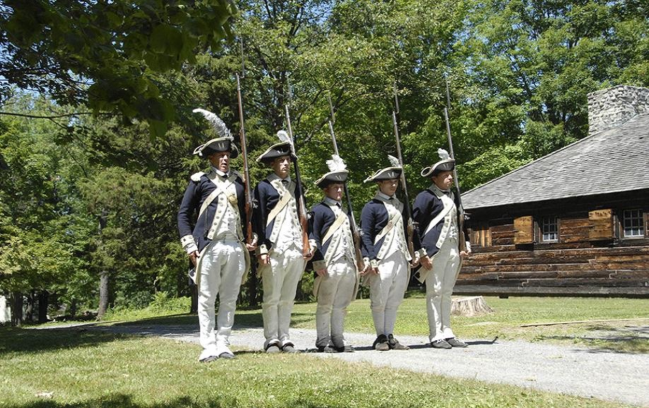 Continental Army soldiers from the 7th Massachusetts Regiment perform a military drill in front of the Temple Building at the New Windsor Cantonment.jpg
