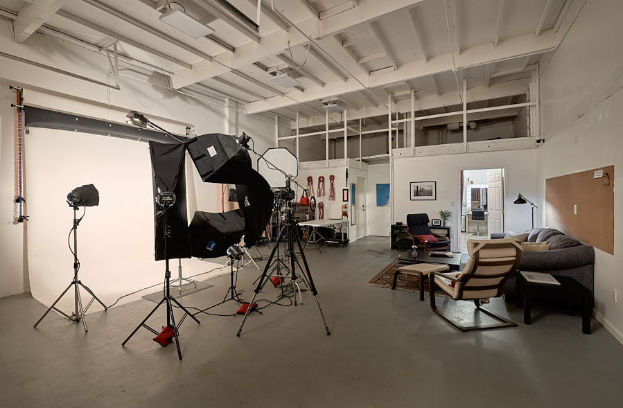 The studio with feminine headshot lighting ready to go. You can see the dressing room and makeup station behind the lounge.