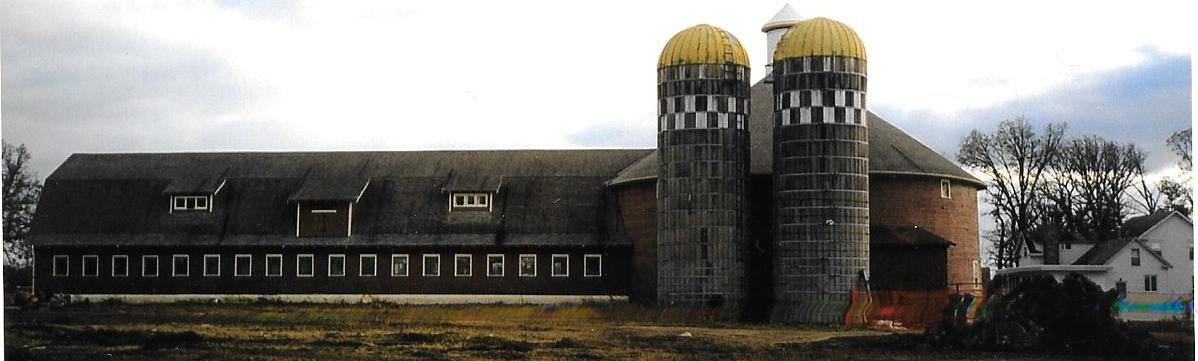 The Original Farm complex. The long barn, on the left of the round barn, the two silos, and the farmhouse seen in the right corner are all gone now, replaced by a senior living complex.