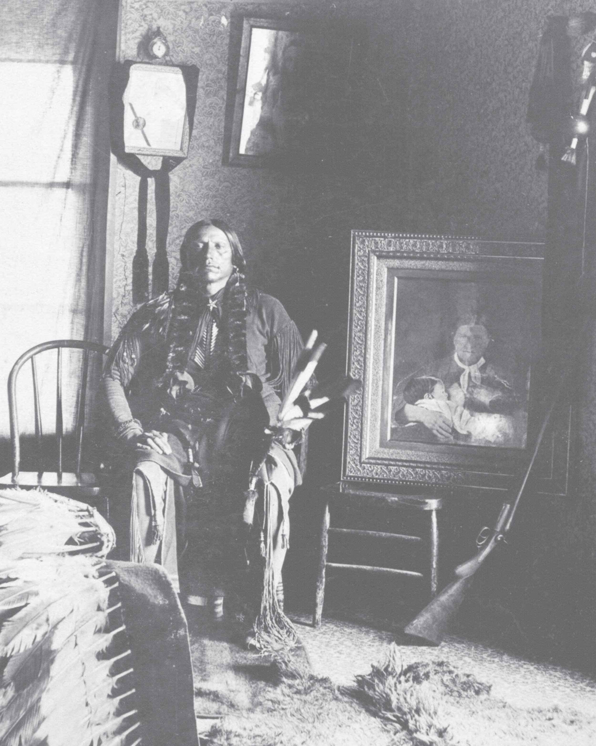 Quanah in his bedroom at Star House, ca. 1897. Next to him is a framed portrait of his mother, Cynthia Ann, and sister, Prairie Flower—his most cherished possession.