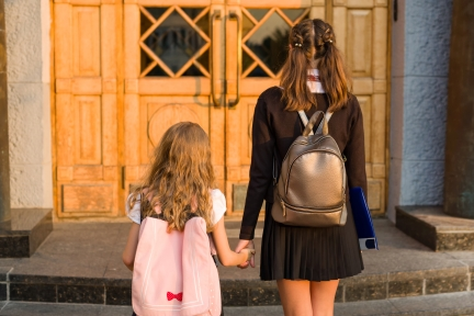 Two girls holding hands going up steps to school