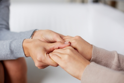 One woman holding tightly to another woman's hands