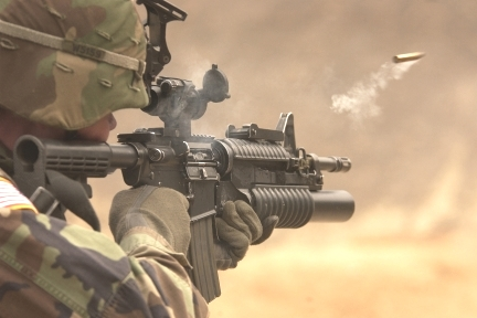 Armed Soldier with Automatic Weapon and Bullet in Air