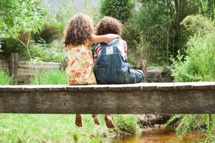 Girl embracing boy while both are sitting on a footbridge