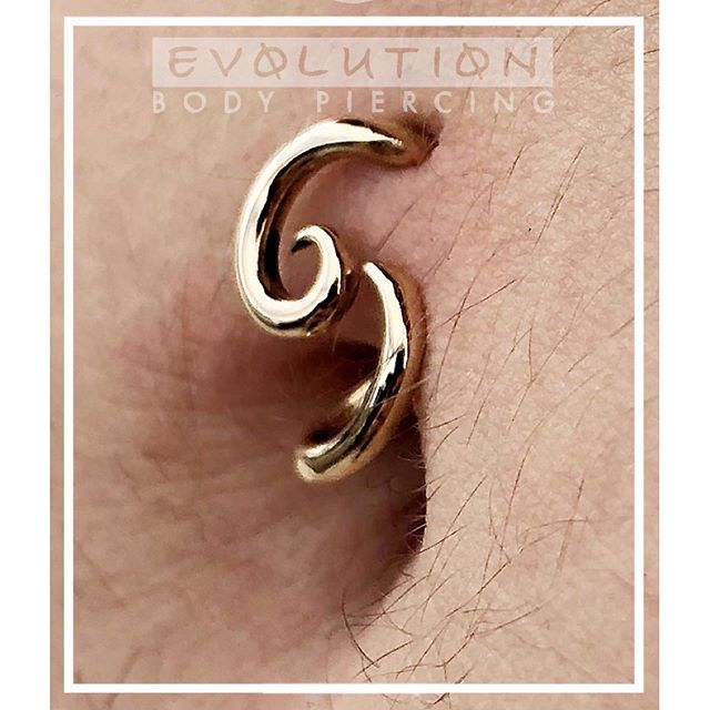 "We love Navels! This one was performed by head Piercer Noah Babcock, who utilized a jaw-dropping 14K yellow gold ""Antares"" from his own line, Interstellar Jewelry Productions. Navels are very popular showcase piercings, especially during spring and summer months. The average healing time for a Navel is 6-9 months, making beach and pool visits a potential health risk when done during the warm weather months. Keeping fresh piercings out of open bodies of water is vital for a successful healing, so now is the perfect time to get one to allow it to heal before your next beach or lake vacation! You can find Noah in the studio doing what he loves best Wednesday-Saturdays, and it would be his pleasure to show you the many stunning options we have in stock! Noah takes walk-ins as time permits between appointments, but you can skip the line when you book an appointment at www.evolutionpiercing.com. @noahbabcock @interstallerjeweryproductions #settingahigherstandard #safepiercing #associationofprofessionalpiercers #navelpiercing #navel #goldjewelry #interstellarjewelryproductions"