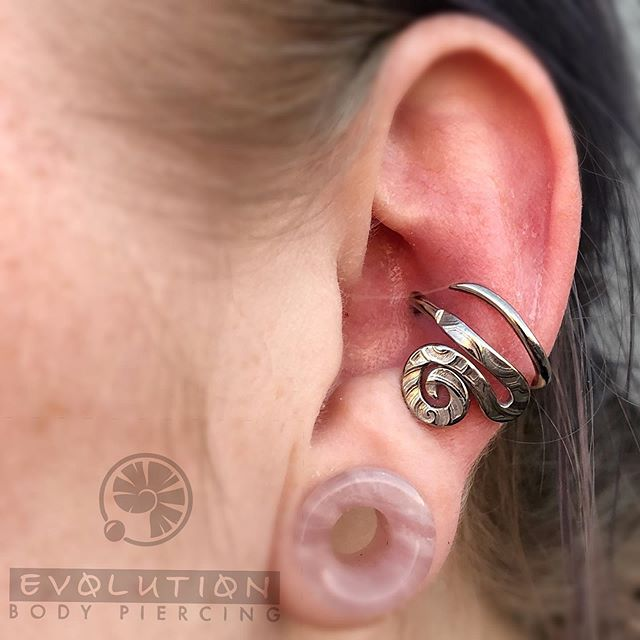 There are many different types of piercings out there, and just as many options for different jewelry styles available. This conch piercing by Noah Babcock features a gorgeous, hammered niobium piece from his own line, Interstellar Jewelry Productions. Conch piercings have been very fashionable this year, and we offer a large variety of ring and stud options in a beautifully diverse variety of materials and sizes. If you'd like Noah to do your piercing, you can book an appointment with him at www.evolutionpiercing.com. He's here Wednesdays through Saturdays, and he and also takes walk-ins as time permits between appointments. November 1st also marks the beginning of our Holiday Food Drive- bring non-perishables with you to get discounts on jewelry and a chance to win a $100 Gift Certificate! Help us beat last year's donation to Road Runner Food Bank that totaled just over 1,000 pounds! #conch #conchpiercing  #safebodypiercing #settingahigherstand #custombodyjewelry #nmlocal #505