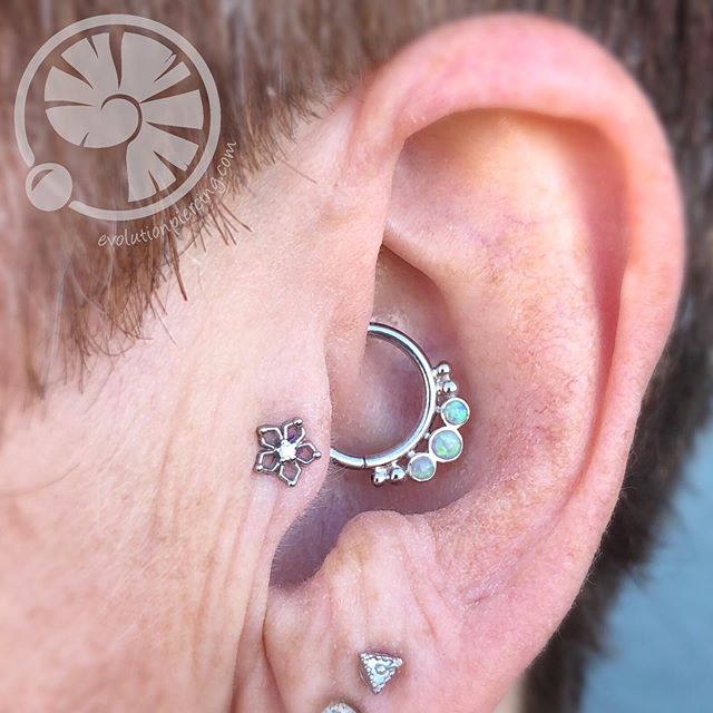 "It's always nice when jewelry looks so different yet pairs so nicely. Here we have a fresh #daith piercing with a white gold and opal ""Barr's"" by @bvla and a fresh #tragus piercing with a white gold ""Flourish"" by @mayajewelry . Both performed by our head piercer @noahbabcock . You can book an appointment online with Noah at www.evolutionpiercing.com #daithpiercing #daithjewelry #traguspiercing #tragusjewelry #evolutionpiercing #505 #burque #newmexicosbest #nmtrue"
