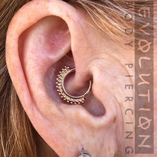 "Here is a daith piercing done by piercer Scott Self done with a stunning ""Kolo"" continuous ring in 14k rose gold from BVLA. This Kolo suits the client's anatomy perfectly, bringing this fresh piercing to life with elegance and style. We have many beaded options like the Kolo in our display case that we would love to show you. Scott is piercing Sunday, Tuesday and Friday each week and is available for walk-ins and appointments through our website, www.evolutionpiercing.com @piercerscott @bvla #evolutionbodypiercing  #settingahigherstandard #gold #rosegold #14kgold #bvla #nmbusiness #appmember #daith #daithpiercing #safepiercing"