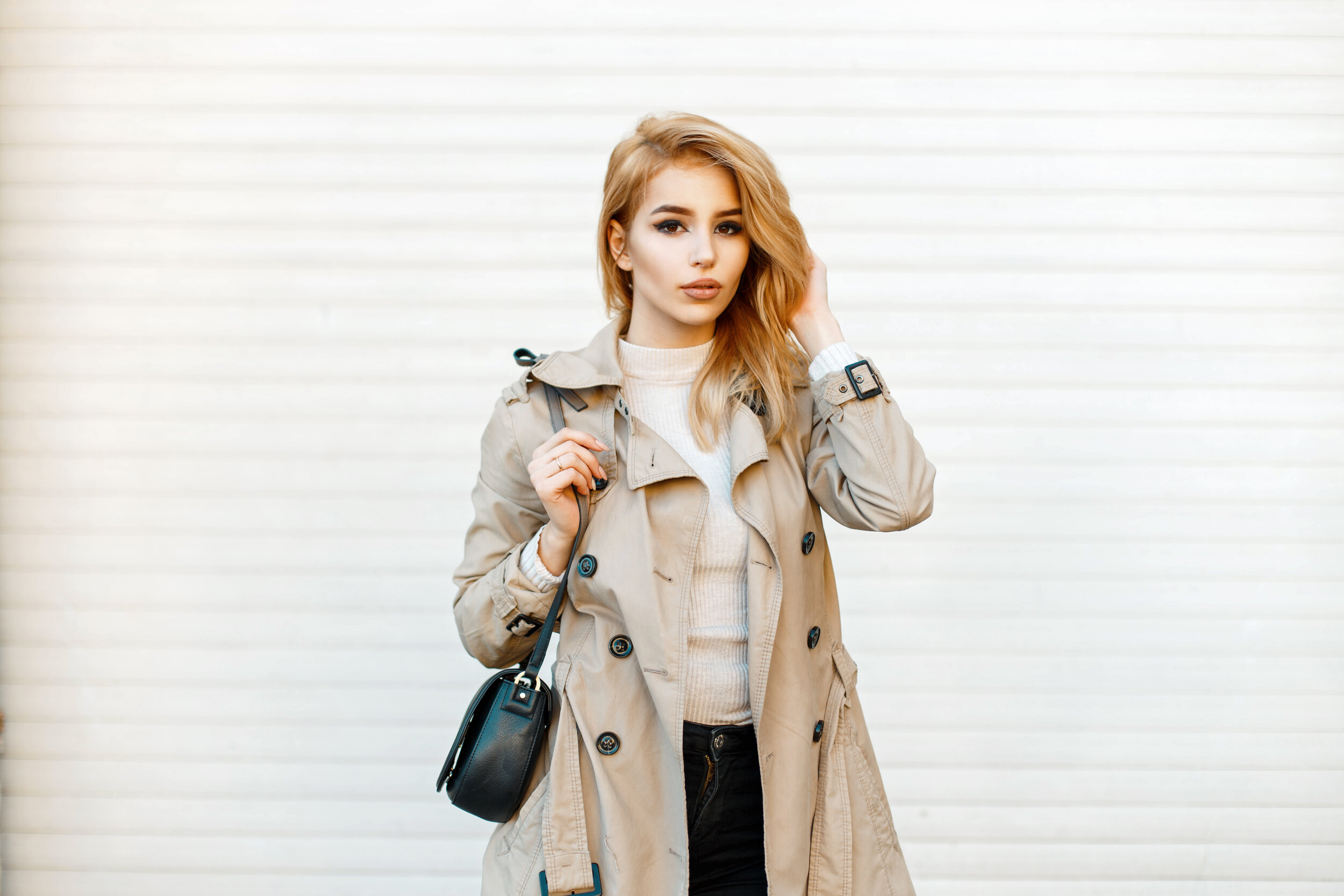 Young woman in trendy coat with handbag near white wall