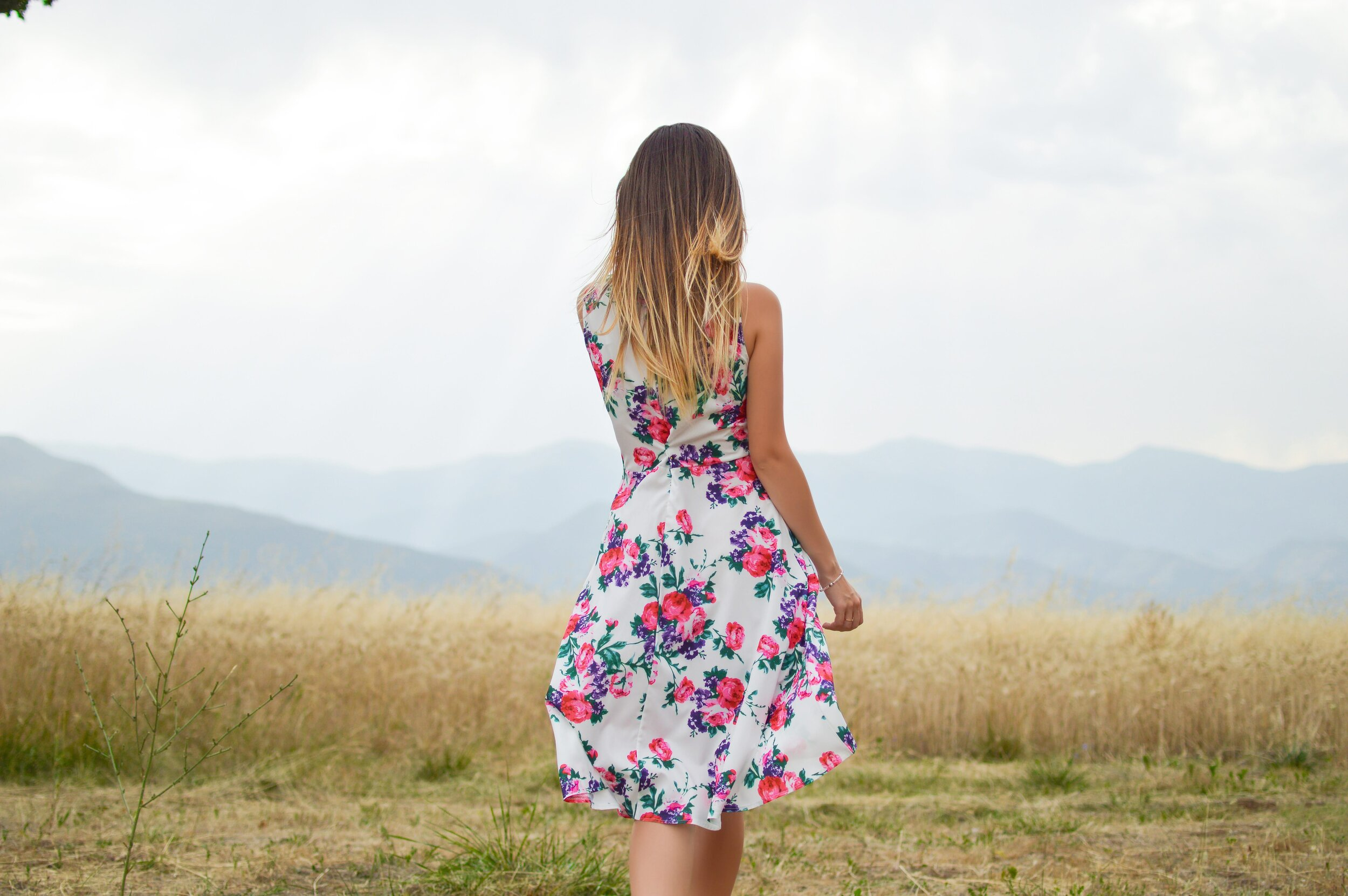 Girl with pear shaped body wearing sleeveless dress with gored skirt to widen shoulders and emphasize waist.