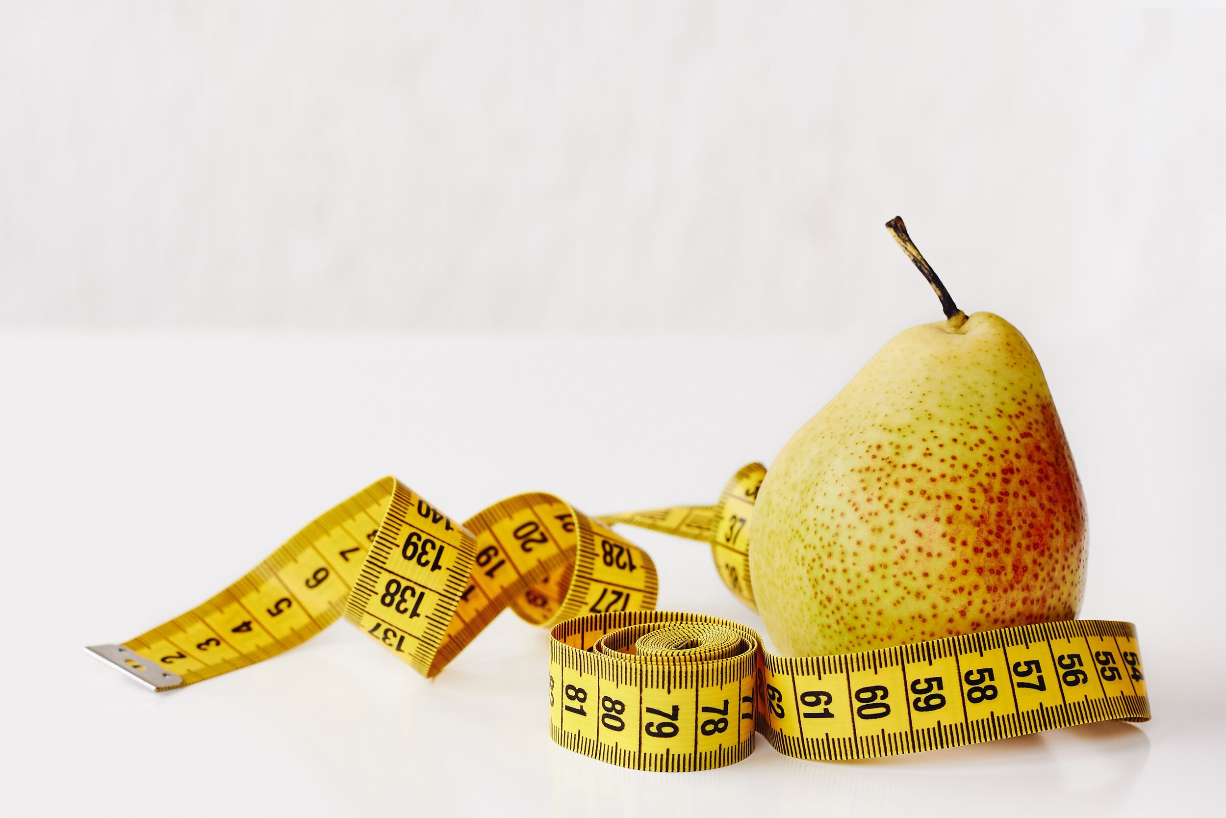 Pear with measuring tape wrapped around. Women's fashion for pear shaped body.