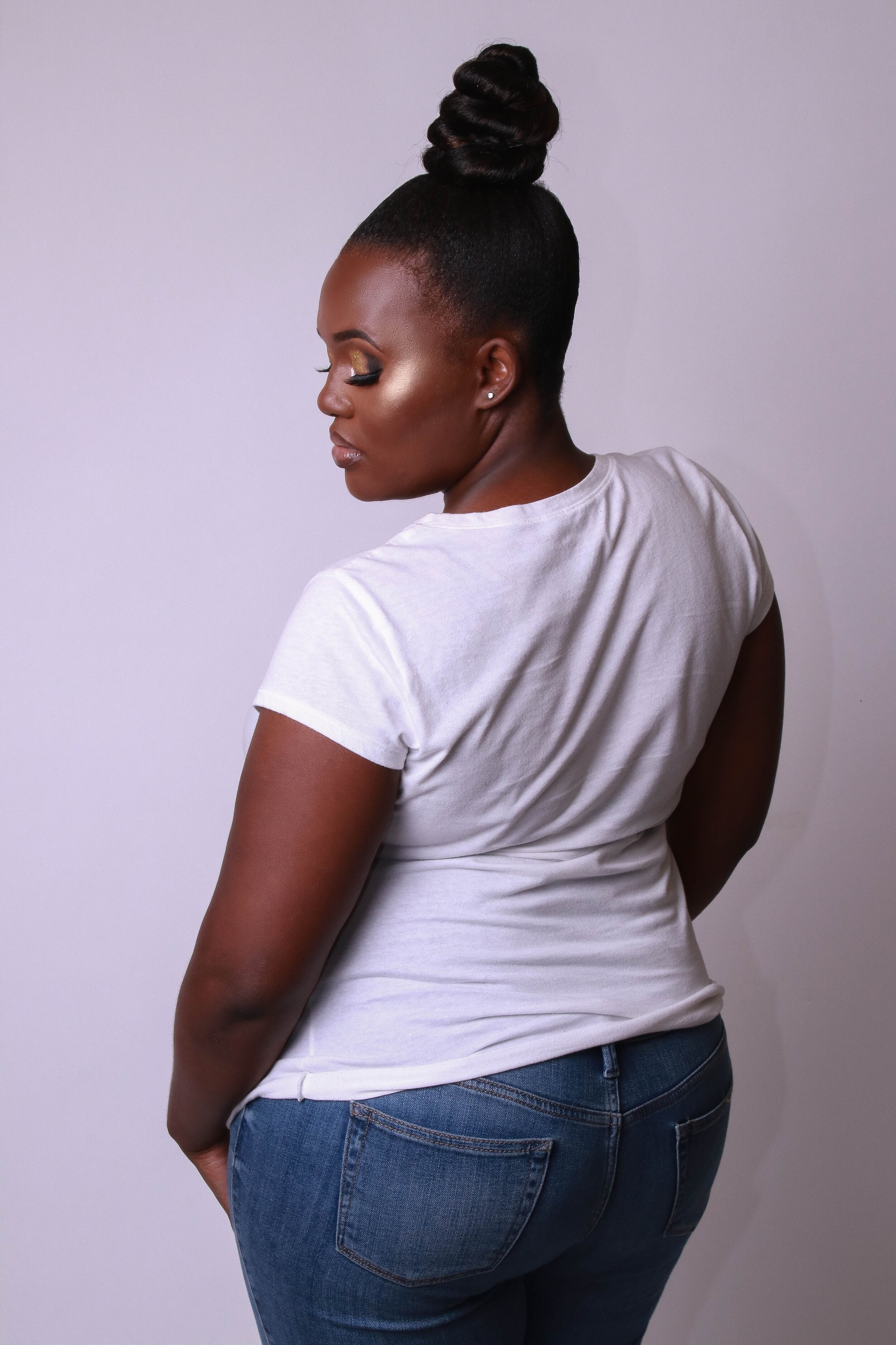 Plus size woman wearing best jeans for pear shape, straight leg dark rinse jeans with large back pockets.