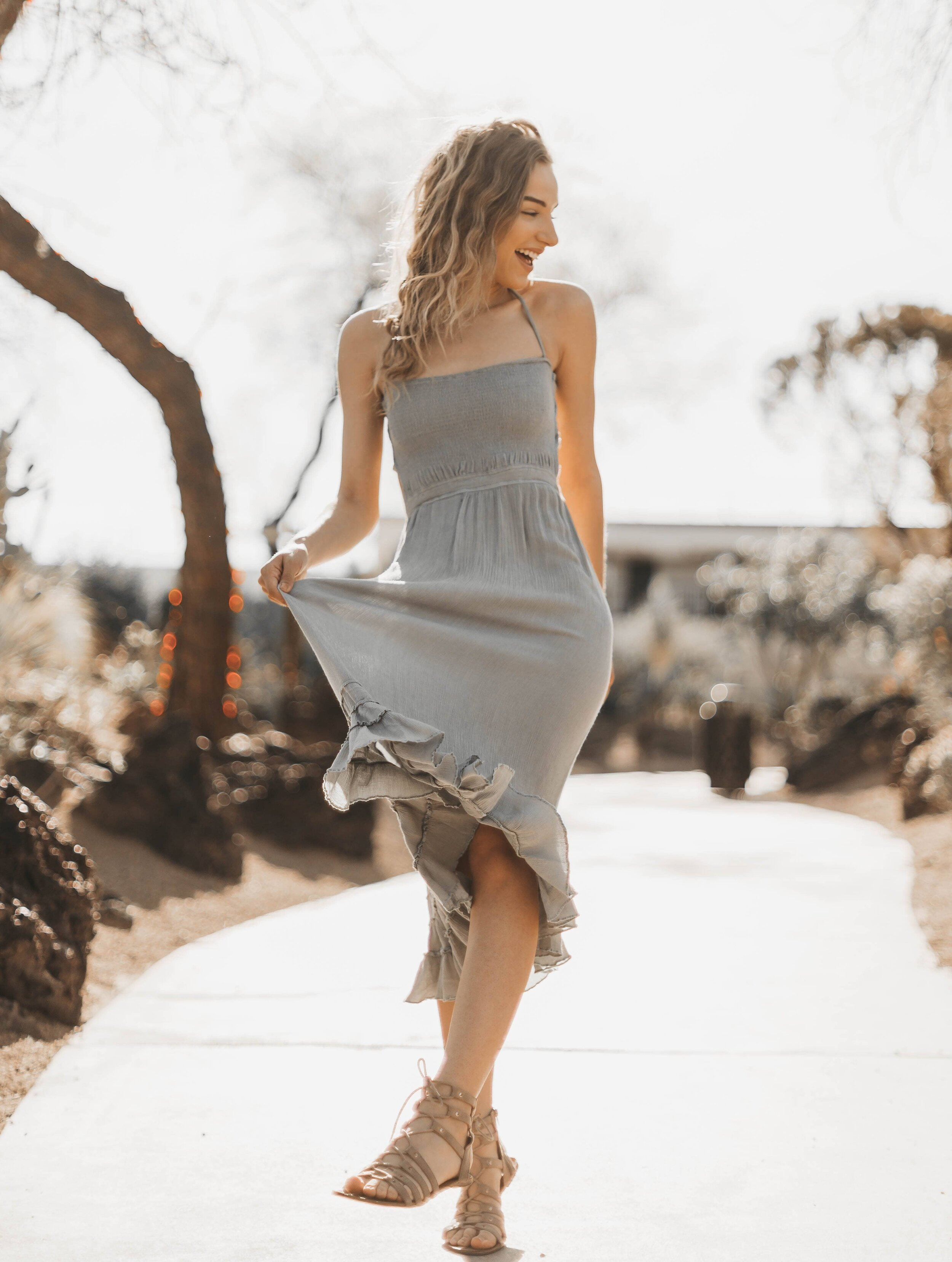 Buying outfits from online clothing boutique was easy, woman in tan sundress happy she found dresses online.
