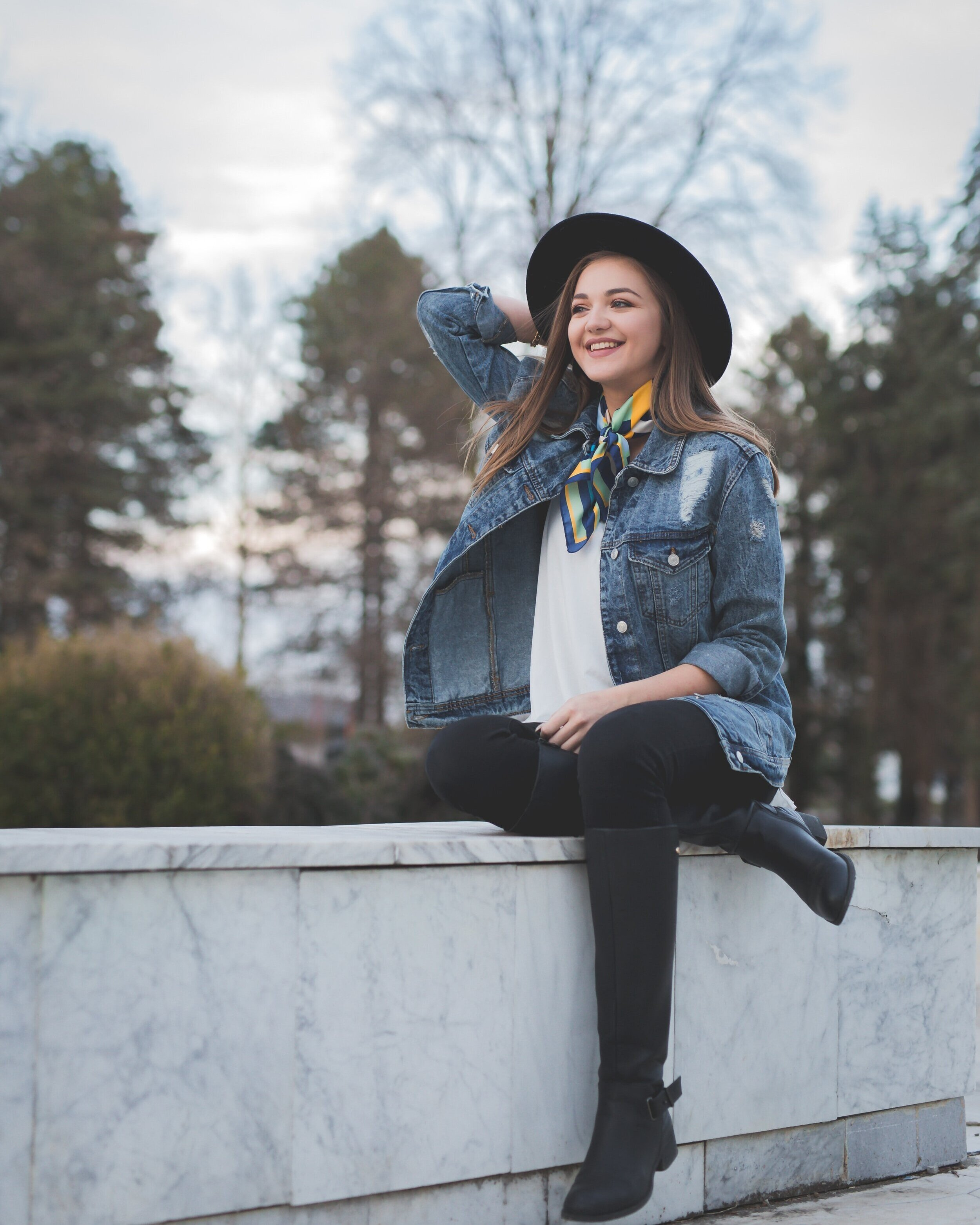 Young lady sitting on marble fence, wearing hat, jean jacket, colorful scarf tied around her neck, black jeans and knee-high boots. What to wear in your 30s is different than fashion for women over 60.
