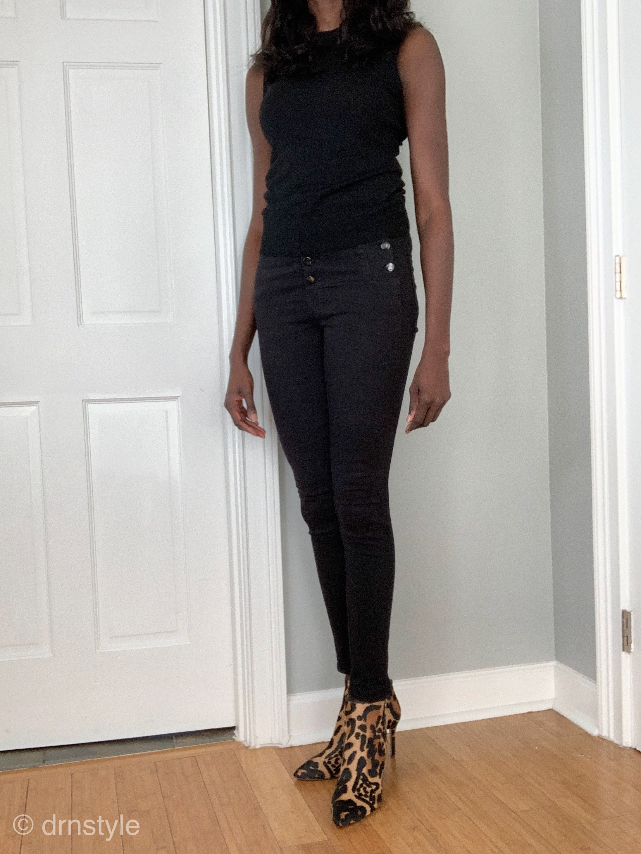 A black sleeveless top, black jeans, and leopard print boots.