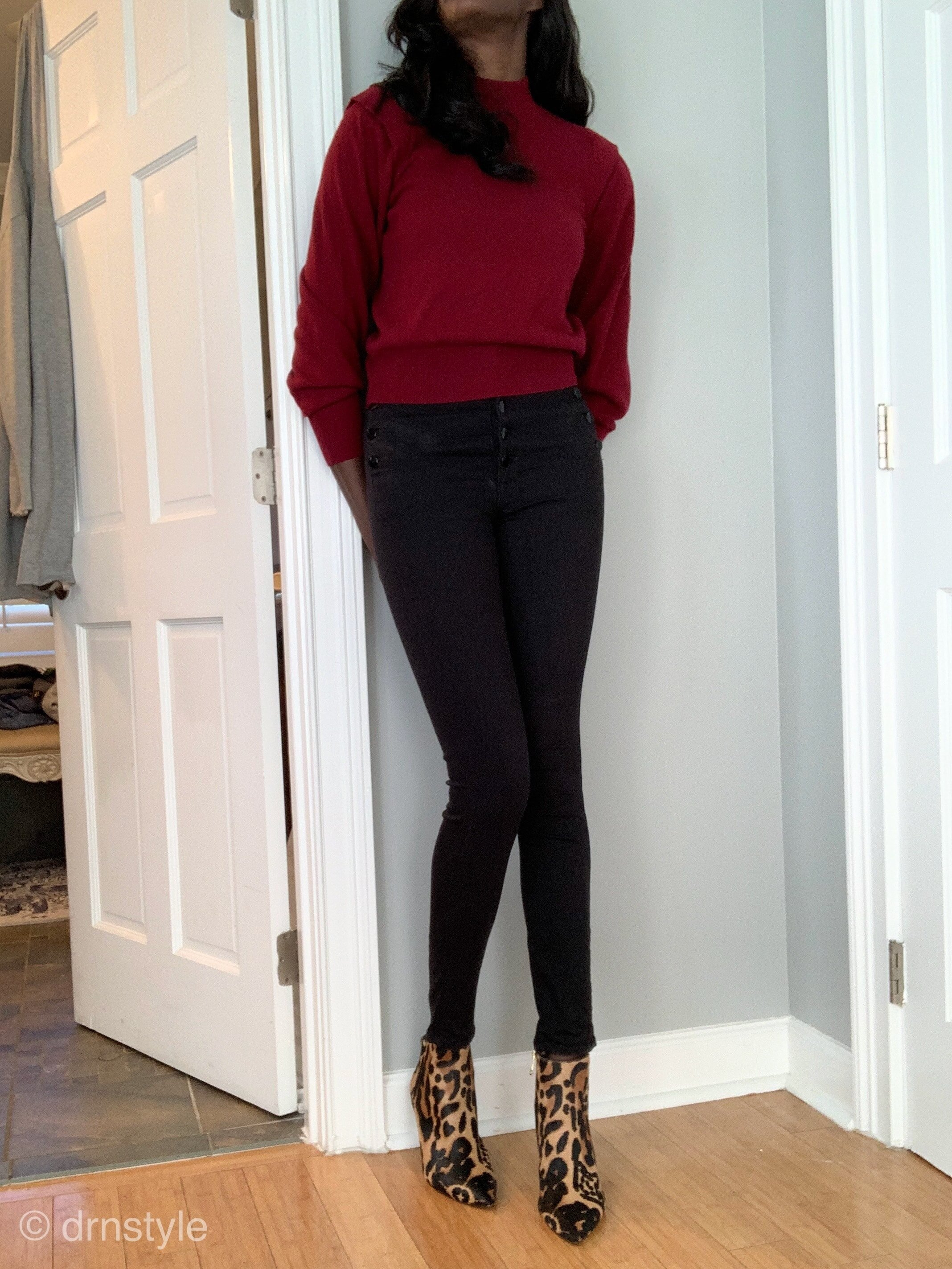 A burgandy sweater with black jeans and leopard print booties.