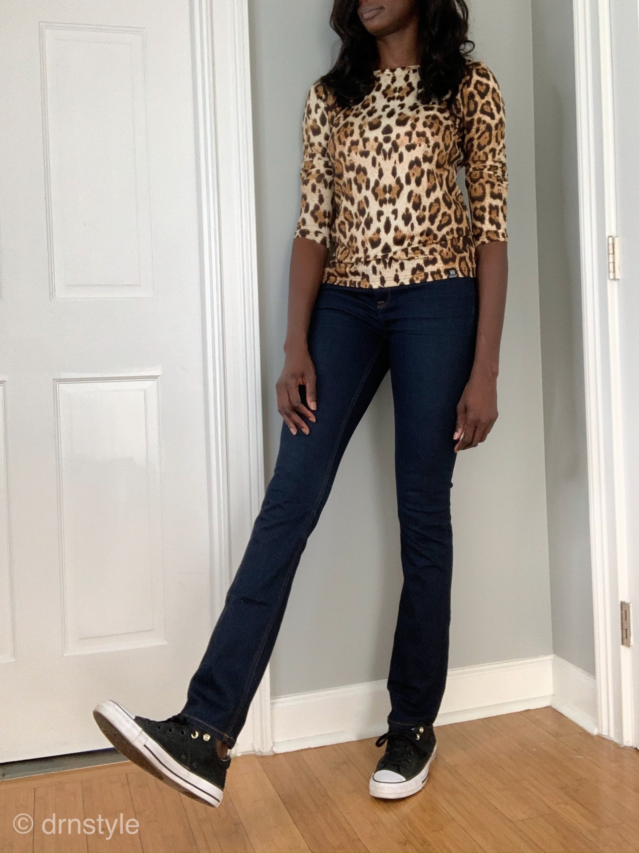 A leopard print top with dark washed jeans and Converse sneakers.