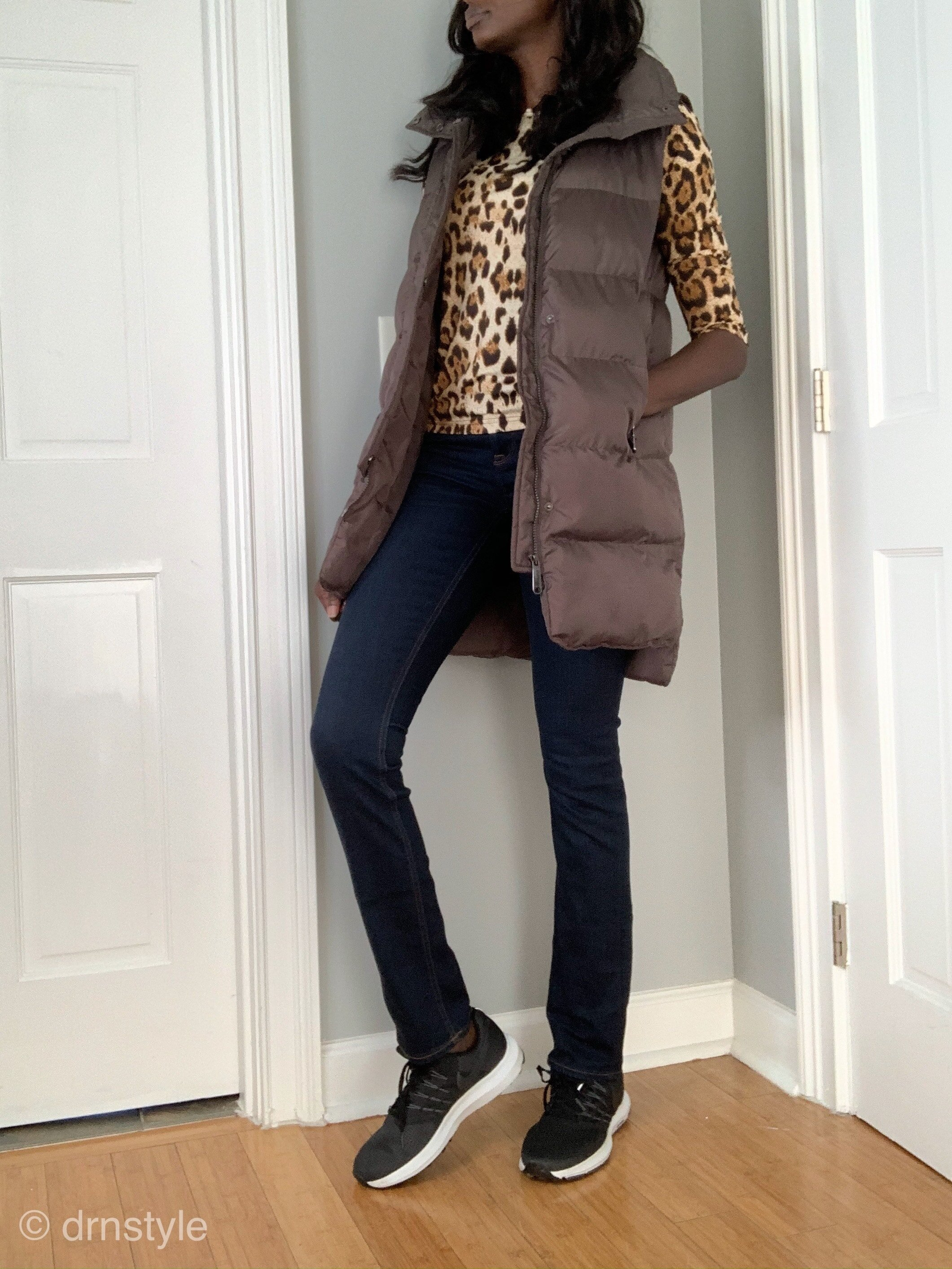 A leopard print top with puffer vest, dark wash jeans and running shoes.