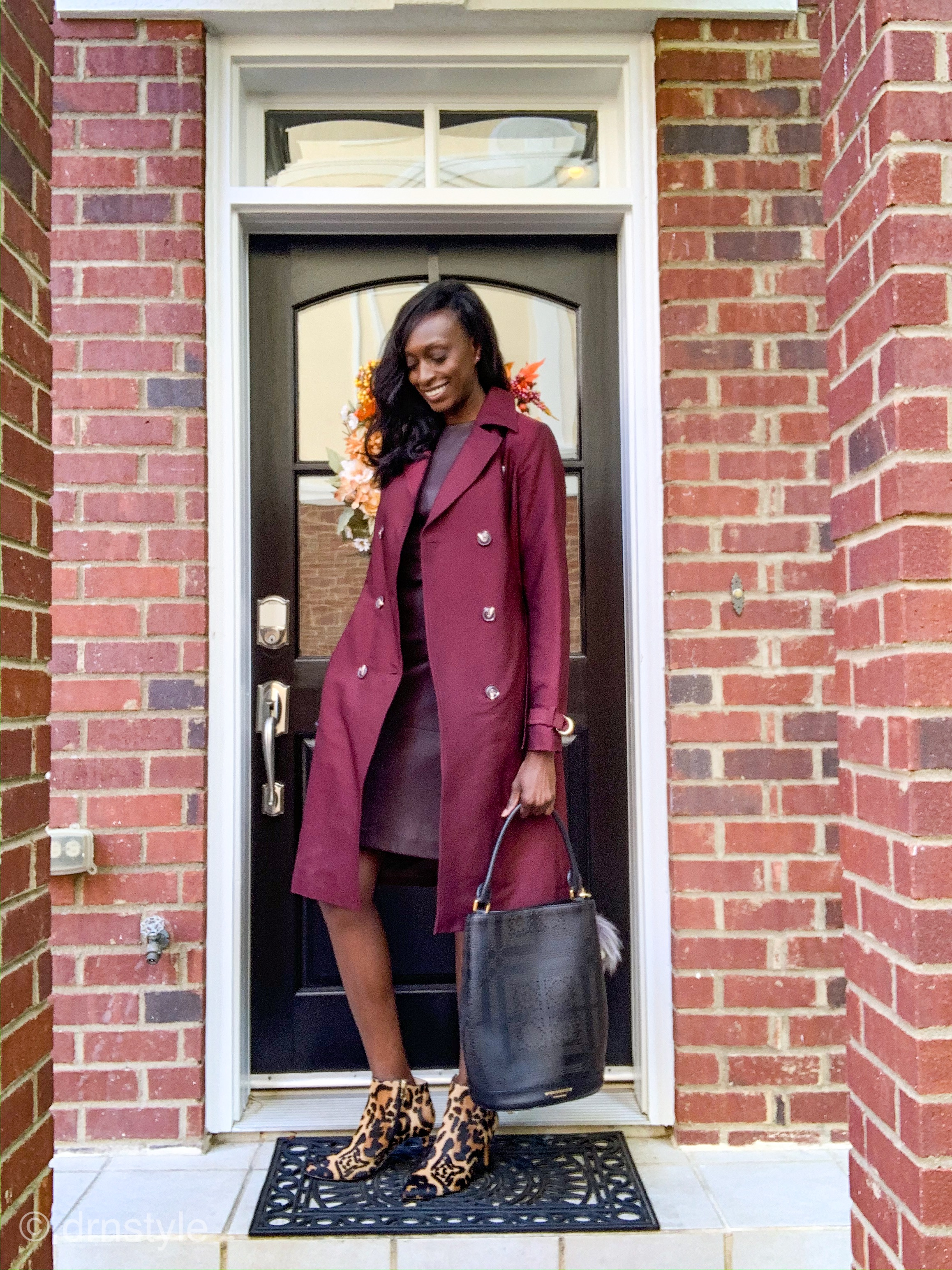 woman wearing a wine colored leather dress, wine colored trench coat, and leopard booties for fall