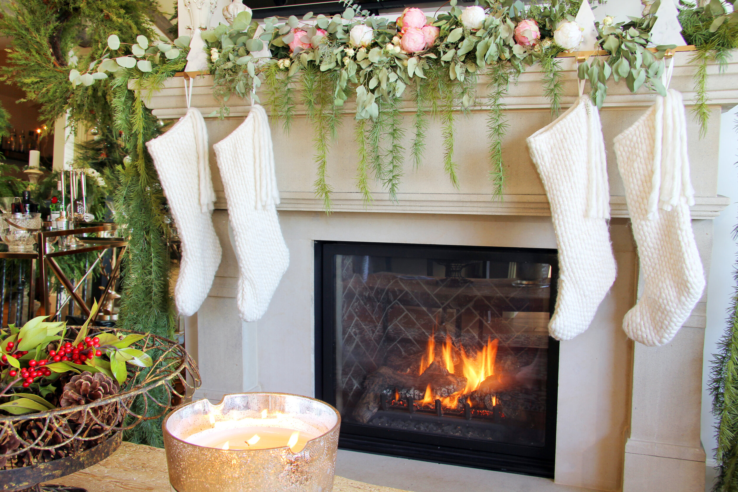 Stocking stuffers or small gifts for women, including mom, sister, grandmother, and daughter to put into the beautiful white stockings hanging from a mantle adorned with pink roses and greenery. A fire is lit in the fireplace with a candle nearby and cart with festive beverages.