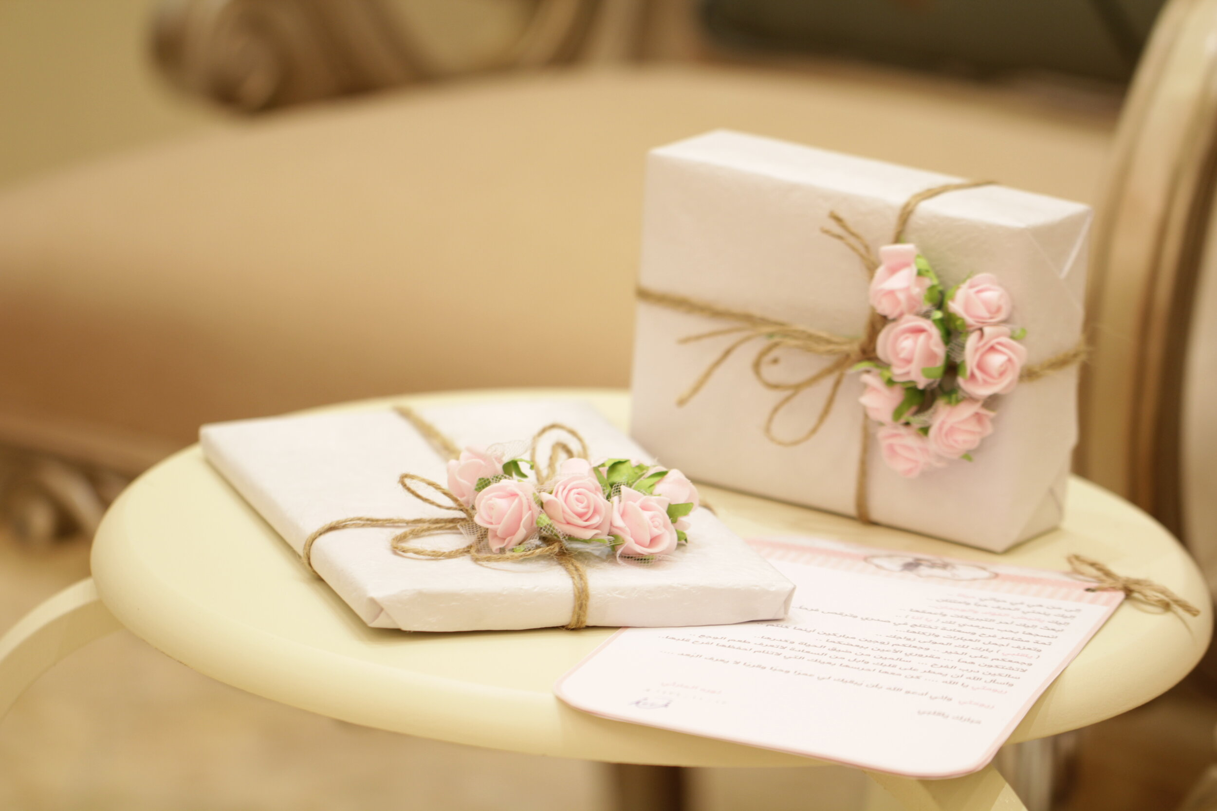 Two gifts on a table, wrapped in white paper tied with string and decorated with pink roses. Do-it-yourself gifts everyone will love.