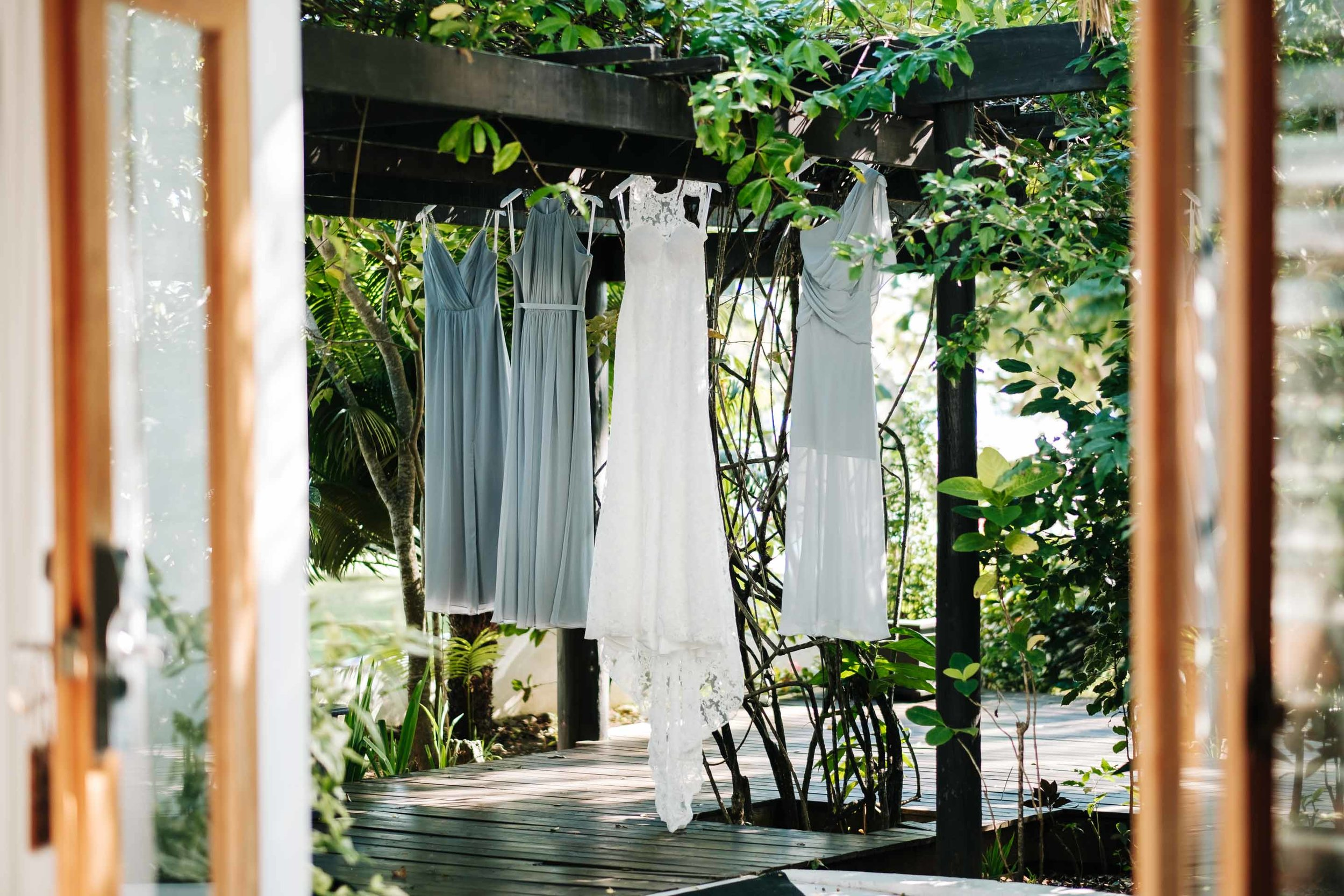 The brides wedding gown by Grace loves Lace with her brides maids dresses hanging from the vine covered pergola outside their room
