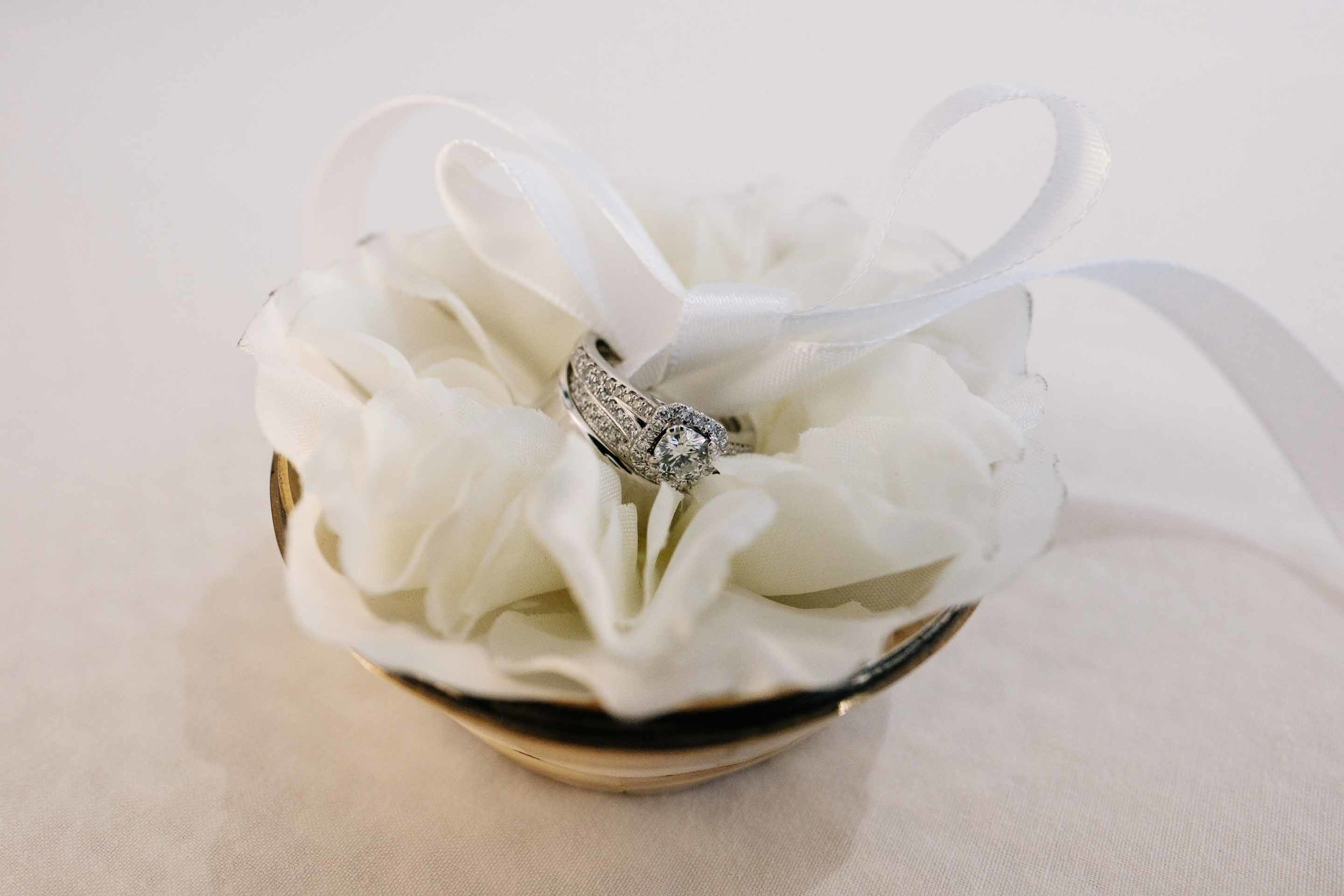 Wedding rings tied together with ribbon in a customised ring holder