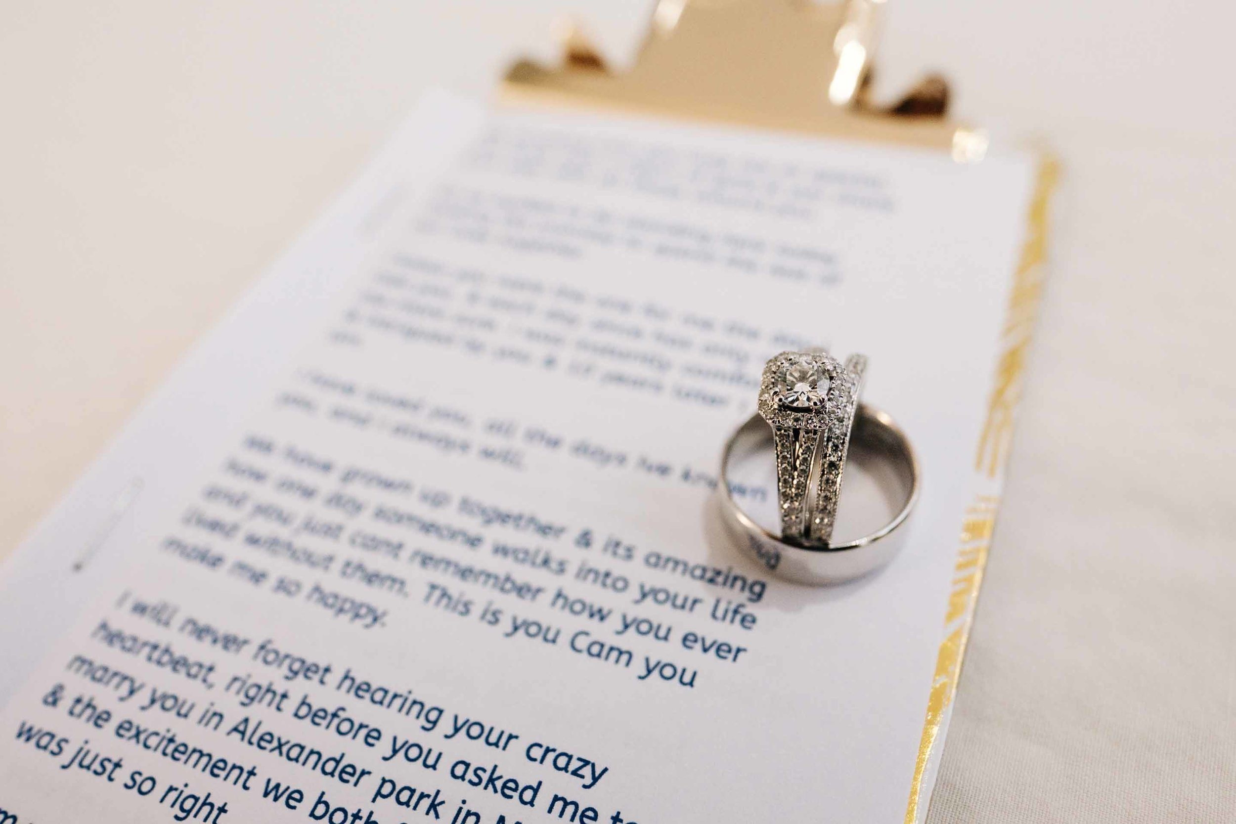 wedding rings placed on the bride Holly's vows neatly printed and placed in a custom gold clipboard