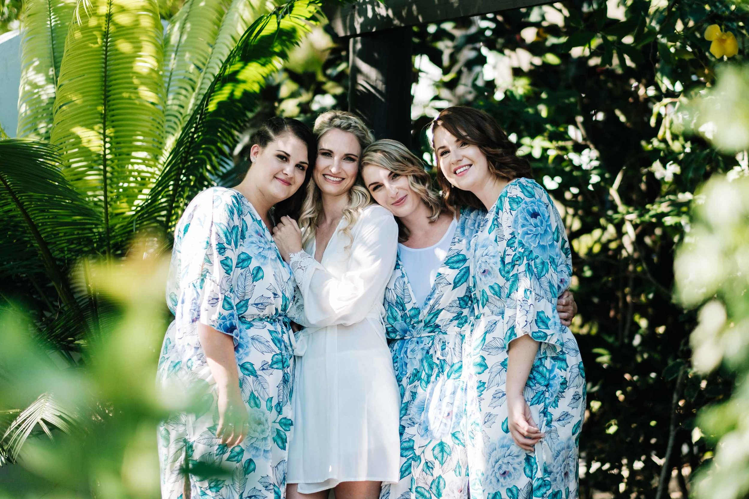 the bride Holly and her bridesmaids in their tropical floral robes outside their room under the pergola
